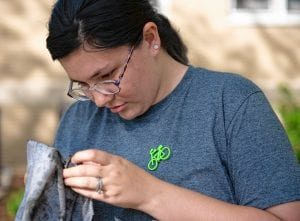 Stephanie Hennrikus, a RAD volunteer cleans a bike part.